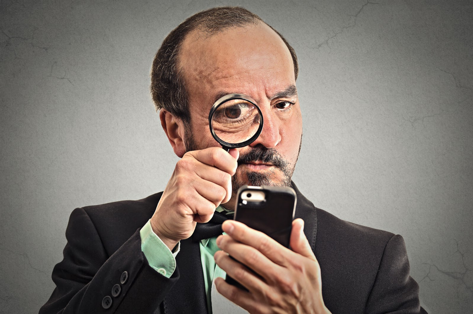 A guy using a magnifying glass to look at a phone
