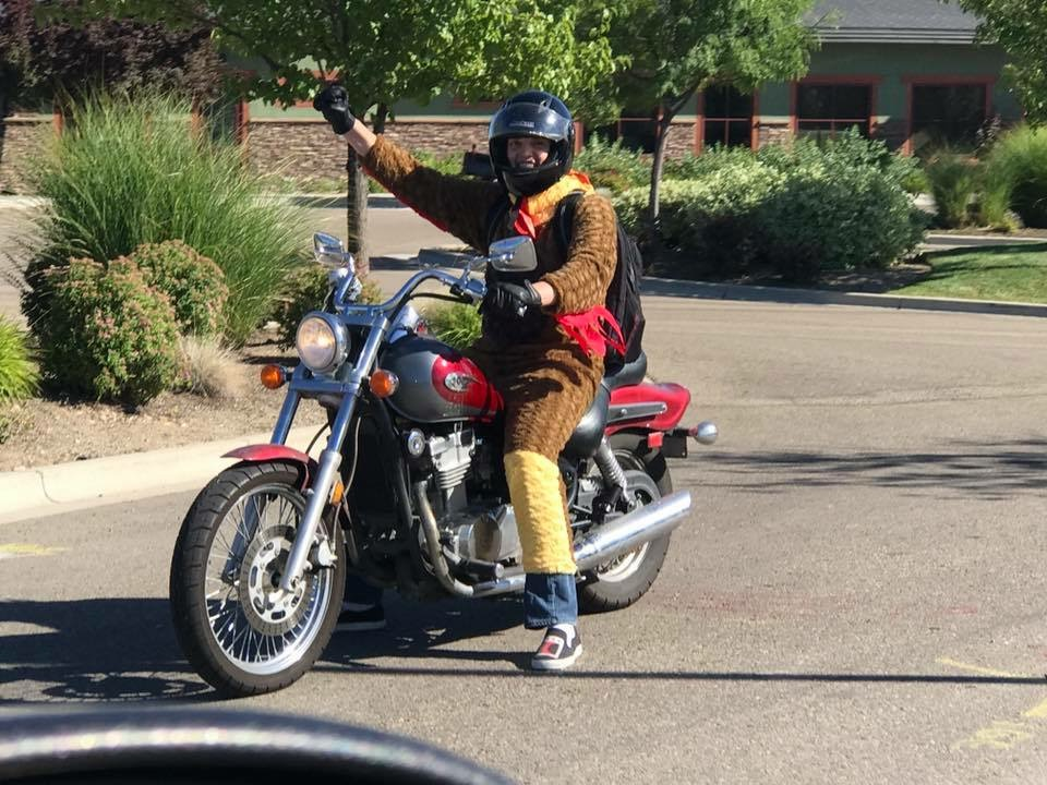 Stephen Larsen on a motorcycle wearing a chicken outfit