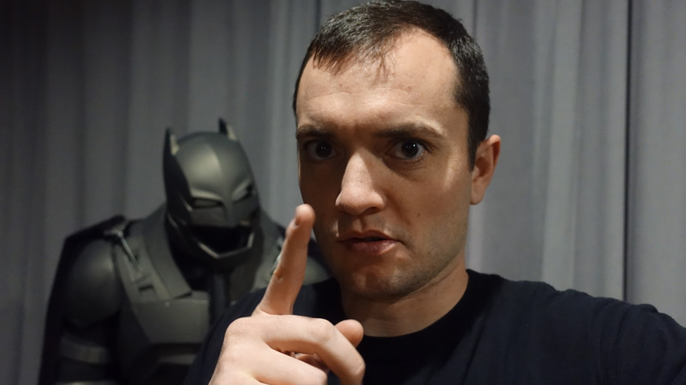 Steve Larsen pointing at the camera with a batman suit behind him