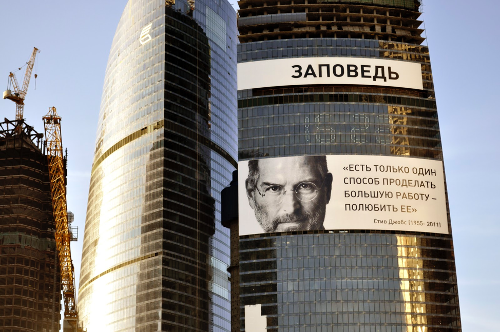 Picture of a billboard on the side of a building that is showing Steve Job's face