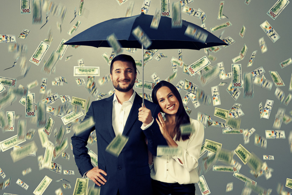 Couple with umbrella and money falling from sky