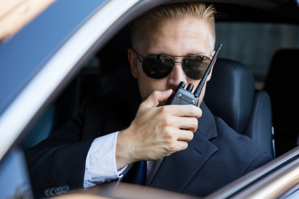 Man in suit in car with walkie talkie