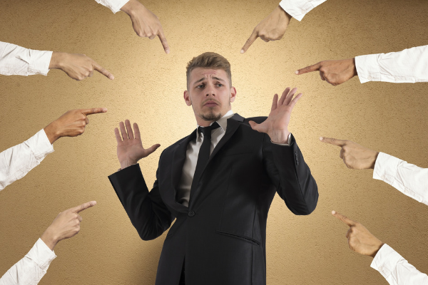 Man in suit with lots of fingers pointing at him