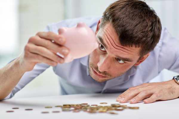 Man looking at empty piggy bank