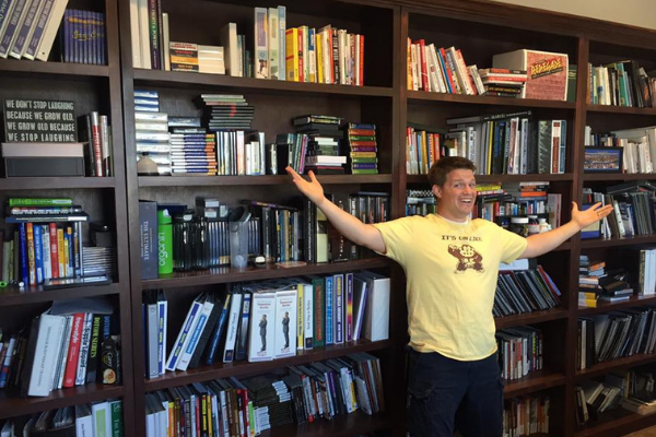 Russell Brunson in front of a lot of books
