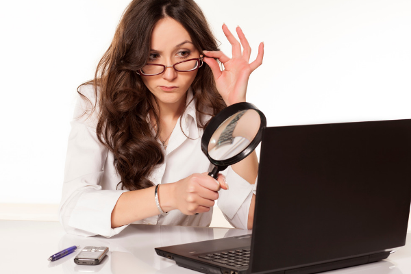 Woman looking through magnifying glass at laptop