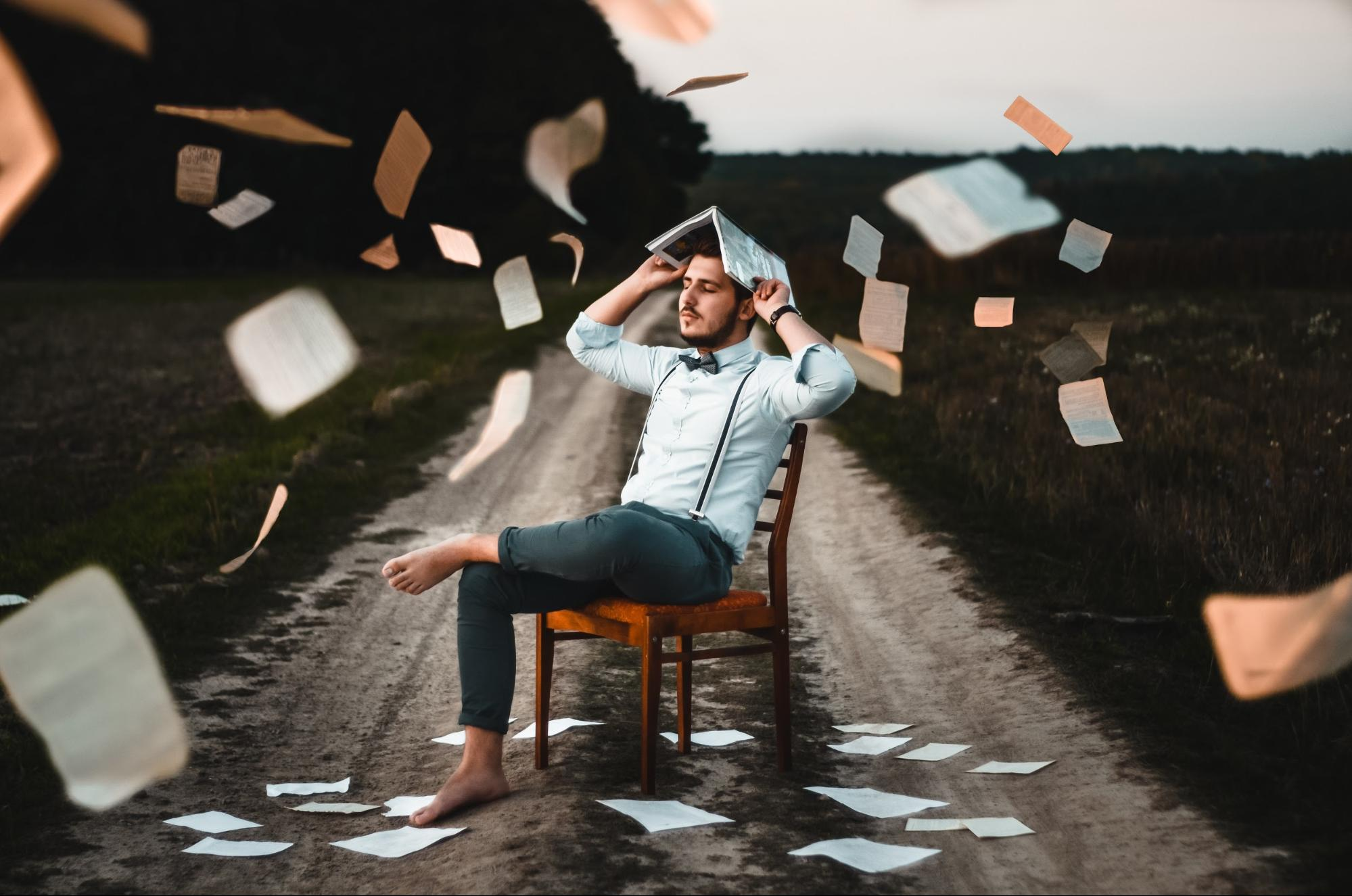 man in chair with papers flying around