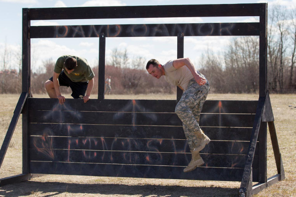 men jumping over obstacle